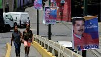 Des femmes marchent près d'une affiche de campagne du président vénézuélien Nicolas Maduro, dans les rues de Caracas, le 11 mai 2018 [Luis ROBAYO / AFP]