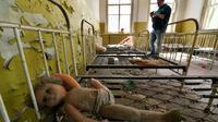 Un touriste prend des photos dans une école maternelle abandonnée dans le village de Kopachi près de la centrale de Tchernobyl le 23 avril 2018 [Sergei SUPINSKY / AFP]