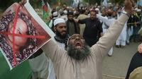 Un partisan du parti musulman extrémiste ASWJ (Ahle Sunnat Wal Jamaat) proteste contre l'acquittement de la chrétienne Asia Bibi dont il brandit le portrait barré de rouge, à Islamabad le 2 novembre 2018 [AAMIR QURESHI / AFP]