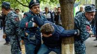 Des policiers arméniens interpellent un manifestant de l'opposition à Erevan, le 20 avril 2018 [Karen MINASYAN / AFP]