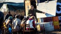"""Un bénévole fait la classe à des enfants migrants dans le camp de la """"Jungle"""" à Calais, le 16 février 2016 [PHILIPPE HUGUEN / AFP/Archives]"""