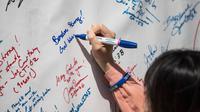 Une femme rédige un hommage en souvenir des victimes des attentats de Boston, le 14 avril 2014 à Boston [Andrew Burton / Getty Images/AFP]