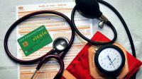 Une feuille de soins, une carte Vitale, un stéthoscope et un tensiomètre dans un cabinet médical [Philippe Huguen / AFP/Archives]