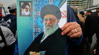 Un Iranien brandit une affiche avec le portrait du guide suprême Ali Khamenei (centre) et de l'ayatollah Rouhollah Khomeiny, père fondateur de la République islamique (en haut à gauche), lors du 40e anniversaire de la Révolution islamique à Téhéran, le 11 février 2019 [ATTA KENARE / AFP]
