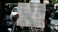 """Une pancarte sur laquelle on peut lire """"Dernier avertissement Nkurunziza, cessez de tuer des gens, nous en avons assez de votre mauvais gouvernement"""", brandie par un manifestant lors des funérailles d'un journaliste à Bujumbura le 20 octobre 2015 [LANDRY NSHIMIYE / AFP/Archives]"""