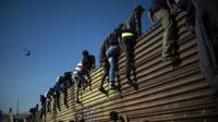 Des migrants centraméricains grimpent sur la barrière métallique marquant la frontière entre le Mexique et les Etats-Unis à Tijuana, le 25 novembre 2018 [Pedro PARDO / AFP]