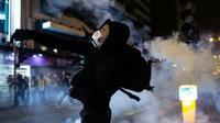Un manifestant dans un nuage de gaz lacrymogènes tiré par la police, le 25 décembre 2019 à Hong Kong [Philip FONG / AFP]