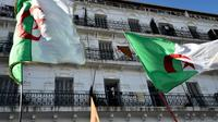 Des drapeaux algériens flottent au vent lors d'un rassemblement contre le pouvoir, le 6 décembre 2019 à Alger [RYAD KRAMDI                         / AFP/Archives]