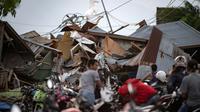 Des indonésiens récupèrent des affaires dans les décombres de leurs maisons après un séisme et un tsunami à Palu, dans l'île des Célèbes, le 29 septembre 2018 [Bay ISMOYO / AFP]