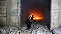 Des Casques blancs, une organisation de secouristes en zone rebelle, luttent contre un incendie après des frappes aériennes sur la ville d'Idleb, le 24 mars 2017 en Syrie [Omar haj kadour / AFP/Archives]