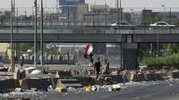 Un drapeau irakien est brandi lors d'une manifestation contre le pouvoir à Bagdad, le 4 octobre 2019 [ / AFP/Archives]