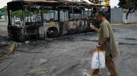 La carcasse calcinée d'une autobus à Caracas le 1er mai 2019 au lendemain au lendemain de l'échec du soulèvement d'un groupe de militaires pro-opposition [Federico PARRA / AFP]