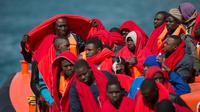 Des migrants enveloppés de couvertures fournies par la Croix-Rouge arrivent à Malaga (Espagne) à bord d'un navire de garde-côtes espagnols qui les a secourus sur leur canot gonflable, le 9 juin 2018 [JORGE GUERRERO / AFP/Archives]