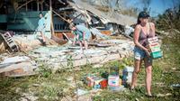 Une famille récupère des marchandises dans une boutique détruite leur appartenant, à Panama City le 11 octobre 2018.  [Emily KASK / AFP]