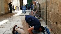 Un palestinien prie à l'extérieur de l'esplanade des Mosquées, le 26 juillet 2017 à Jérusalem [AHMAD GHARABLI / AFP]