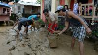 Les habitants enlèvent la boue le 20 octobre 2015 dans les rues de Cabanatuan City, au nord de Manille, apportée par les fortes pluies occasionnées par le typhon Koppu qui a fait au moins 22 morts [TED ALJIBE / AFP]