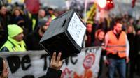 Un homme tient une caisse pour soutenir les grévistes, dans une manifestation à Paris le 26 décembre 2019 [STEPHANE DE SAKUTIN / AFP/Archives]