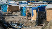 """Un homme assis au milieu de cabanes de fortune dans la """"Jungle"""" de Calais, le 16 mars 2016 [DENIS CHARLET / AFP/Archives]"""