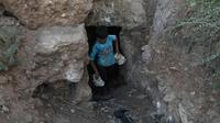 Un enfant transporte des pierres durant des travaux de construction d'un abri souterrain, dans la province syrienne d'Idleb, le 15 septembre 2018 [OMAR HAJ KADOUR / AFP]