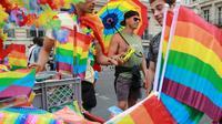 Un homme vend des drapeaux couleur arc-en-ciel lors de la gay pride à Paris, le 24 juin 2017 [JACQUES DEMARTHON / AFP]