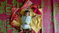 Un bébé dort sur une natte dans un camp d'Aluva, près de Cochin, au Kerala le 20 août 2018 [MANJUNATH KIRAN / AFP]