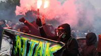 """Des manifestants vêtus de noir et cagoulés, à la manière des """"black blocs"""", défilent lors du 1er mai 2018 à Paris [Alain JOCARD / AFP/Archives]"""