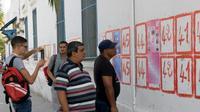 Des Tunisiens regardent des listes de candidats aux élections collées à un mur de la capitale Tunis, le 14 septembre 2019 [Fethi Belaid / AFP]