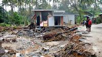 Des Indiens regardent une habitation détruite par un glissement de terrain dans le village de Kannapanakundu, dans l'Etat du Kerala (sud), le 18 août 2018 [MANJUNATH KIRAN / AFP]