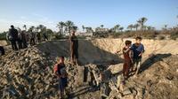 Des enfants palestiniens marchent autour d'un cratère creusé par une frappe israélienne, dans le sud de la bande de Gaza, le 2 novembre 2019 [SAID KHATIB / AFP]