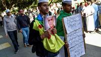 Des Algériens manifestent, brandissant le drapeau amazigh et un portrait du militant des droits humains, Kamel Eddine Fekhar, à Alger le 31 mai 2019 [RYAD KRAMDI                         / AFP]
