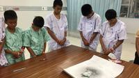 Photo prise le 14 juillet et diffusée le 15 juillet par le ministère de la Santé montre des jeunes footballeurs rescapés d'une grotte en Thaïlande avec un portrait du plongeur mort à l'hôpital de Chiang Rai Prachanukroh [Handout / Chiang Rai Prachanukroh Hospital/AFP]