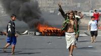 """Un Yéménite fait le """"V"""" de la victoire  en passant près de pneus incendiés lors de manifestations contre l'inflation et le coût de la vie, à Aden, dans le sud du Yémen, le 8 septembre 2018 [Saleh Al-OBEIDI / AFP]"""