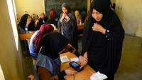 Une employée électorale enregistre l'empreinte biométrique d'une votante lors des législatives, le 20 octobre 2018 à Hérat, en Afghanistan [HOSHANG HASHIMI / AFP]