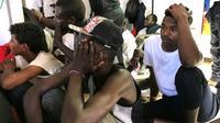 Des migrants secourus par le navire Ocean Viking en Méditerranée attendent à  bord, le 21 août 2019 [Anne CHAON / AFP]