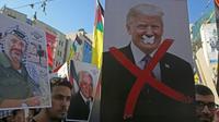 Des manifestants palestiniens avec des portraits de l'ancien leader palestinien Yasser Arafat et du président américain Donald Trump lors d'un rassemblement dans la ville de Naplouse, en Cisjordanie occupée, le 18 juillet 2018 [Jaafar ASHTIYEH / AFP/Archives]