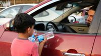 Un garçon irakien essaye de vendre des bouteilles d'eau dans une rue de Mossoul, où des enfants orphelins errent pour mendier ou vendre des objets futiles pour survivre, un an après la reprise par l'armée irakienne de la ville aux jihadistes, le 7 juillet 2018 [Waleed AL-KHALID / AFP Photo]