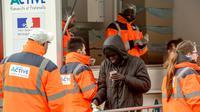 Des bénévoles de l'association La Vie Active distribuent des repas à des migrants à Calais, le 6 mars 2018 [PHILIPPE HUGUEN / AFP]