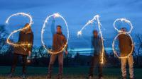 Les célébrations pour l'entrée en 2018 vont débuter en Australie. Photo d'illustration de quatre personnes dessinant 2018 à Sieversdorf, en Allemagne, le 27 décembre 2017 [Patrick Pleul / dpa/AFP/Archives]