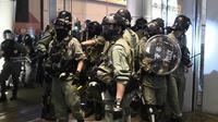 Des policiers sortent du centre commercial Langham Place après y avoir cherché des manifestants, le 26 déceùbre 2019 dans le quartier de Mong Kok, à Hong Kong [Philip FONG / AFP]