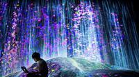 Un membre du collectif japonais teamLab près d'une cascade de lumière au Mori Building Digital Art Museum, le 1er mai 2018 à Tokyo [Behrouz MEHRI / AFP]
