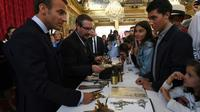 Le président Emmanuel Macron (G) rencontre des jeunes visiteurs à l'Elysée, lors des journées du patrimoine, le 15 septembre 2018 [Anne-Christine POUJOULAT             / POOL/AFP]