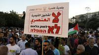 """Des Arabes israéliens manifestent contre une loi controversée définissant Israël comme """"l'Etat-nation du peuple juif"""", le 11 août 2018 à Tel-Aviv [Ahmad GHARABLI / AFP]"""