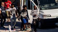 Vingt-sept migrants mineurs non-accompagnés, secourus par le navire de l'ONG espagnole Proactiva Open Arms, sont conduits vers des véhicules de la police italienne avant de quitter le port de Lampedusa où ils ont débarqué le 17 août 2019 [Alessandro SERRANO / AFP]