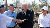 Le président américain Donald Trump (au centre), avec sa femme Melania à ses côtés et le gouverneur de Floride Rick Scott (à gauche) constatent les dégâts après le passage de l'ouragan Michael, à Lynn Haven, le 15 octobre 2018 [SAUL LOEB / AFP]