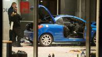 Des policiers inspectent les dégâts provoqués par un homme qui a foncé avec sa voiture contre le siège du SPD, le 25 décembre 2017 à Berlin [Odd ANDERSEN / AFP]