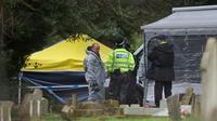 Des enquêteurs dans le cimetière de Salisbury, dans le sud de l'Angleterre, où reposent l'épouse et le fils de l'ancien espion  russe Sergueï Skripal. Le 10 mars 2018. [Daniel LEAL-OLIVAS / AFP]