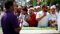 Des hommes prient autour des cercueils contenant les corps d'un imam et de son assistant tués par balles, à New York le 15 août 2016 [KENA BETANCUR / AFP]