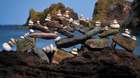 """Photo prise le 21 avril 2019 à Dunbar (Ecosse) où  se tenait une compétition de """"stone stacking"""", l'art de faire tenir les pierres en équilibre  [Andy Buchanan / AFP]"""