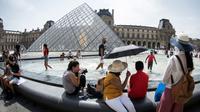 Touristes se rafraîchissant à la fontaine face à la pyramide du Louvre, à Paris le 7 août 2018 [GERARD JULIEN / AFP/Archives]