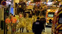 Des victimes, des pompiers et des policiers aux abords du Bataclan à Paris dans la soirée du 13 au 14 novembre 2015 [MIGUEL MEDINA / AFP/Archives]